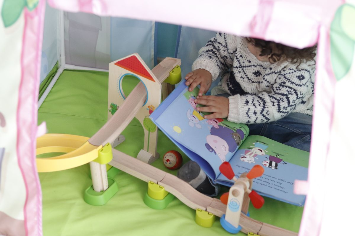 leyendo libros y jugando dentro de la casita de tela