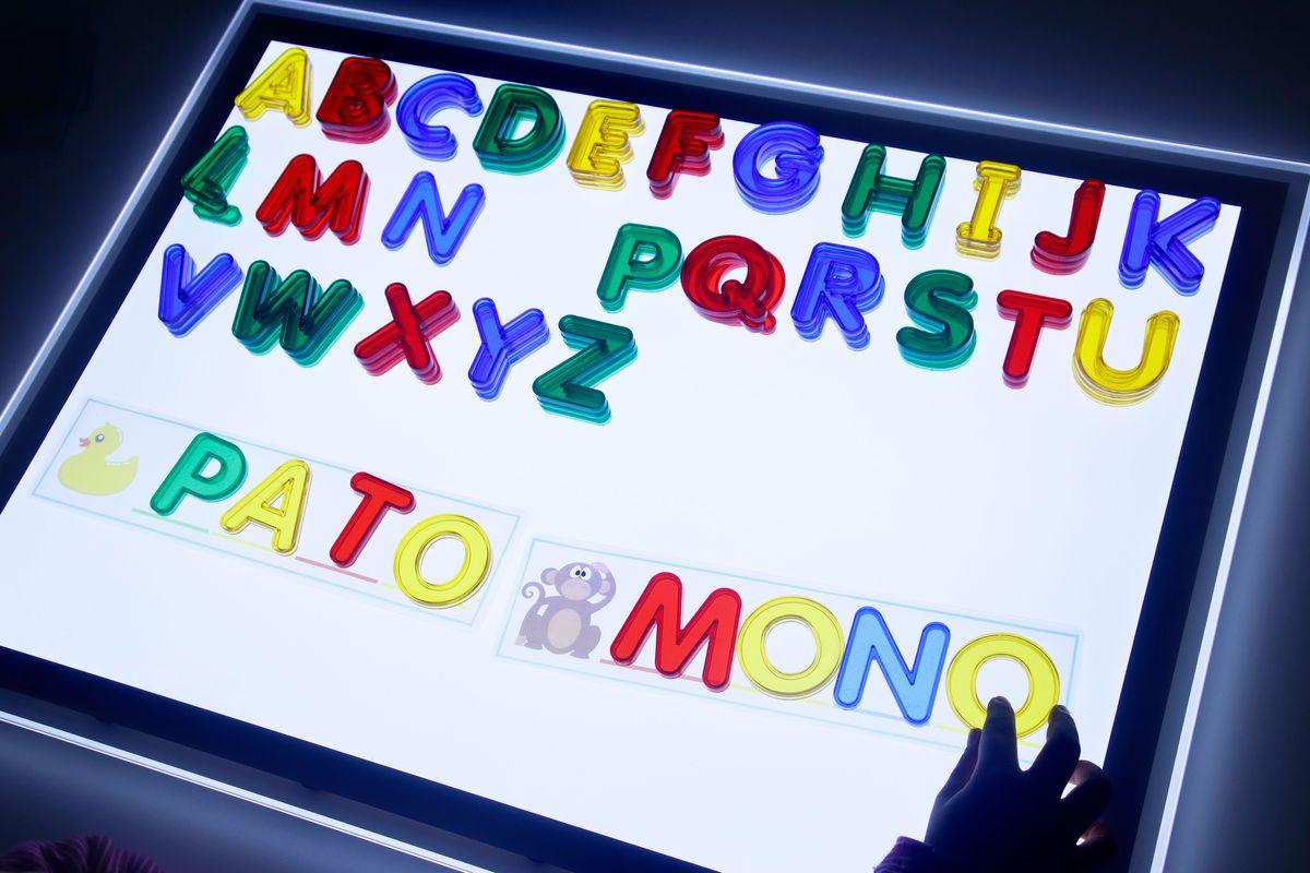 Escribiendo palabras en la mesa de luz con las letras translúcidas