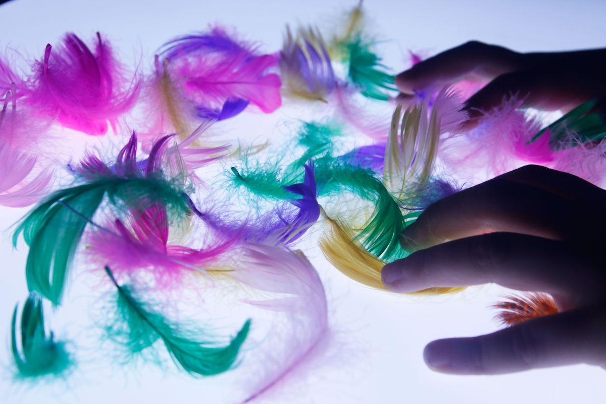 plumas de colores en la mesa de luz