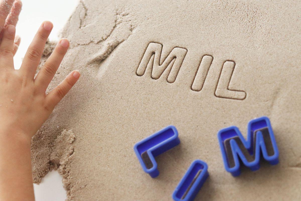 escribiendo-en-arena-con-moldes-de-letras-de-cocina